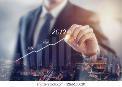 Growth in 2019 year concept. Businessman plan growth and increase of positive indicators with city background, Double exposure.