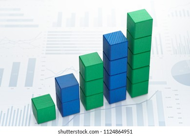 Growth chart. Gathering statistics and analyzing data. Toy block steps on many charts and graphs background.