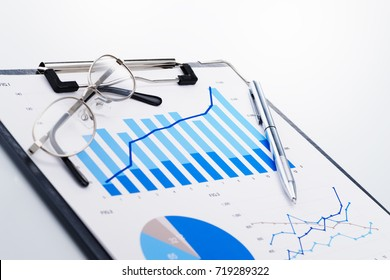 Growth chart. Reviewing business report. Concept image of analyzing data. Documents and glasses on white reflection background.