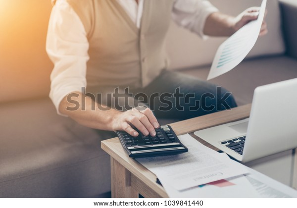 Growth investor auditor graphs bill people think insurance job entrepreneur paperwork plan stock shares person notebook concept. Close up photo of shareholder's hand using pressing buttons calculator