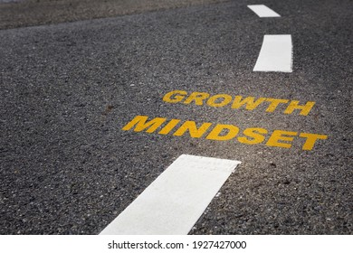 Growth mindset written on asphalt road surface. Self development to success concept and challenge keep moving idea