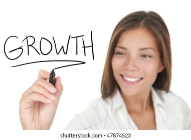 Growth and success in business concept. Young beautiful businesswoman with pen writing growth on whiteboard. Focus on black marker. Mixed race Chinese / Caucasian model isolated on white background
