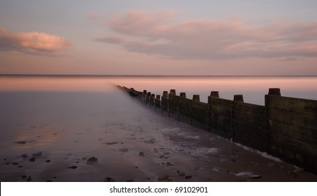 A groyne juts out into the sea on a peaceful spring evening. Photograph taken with a neutral density filter to enable long exposure.