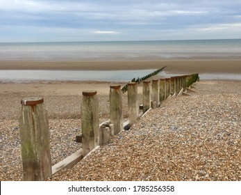 Groynes on Winchelsea Beach to stop the erosion by the tides and weather. Pebble beach with sea and sky landscape - East Sussex UK near Rye
