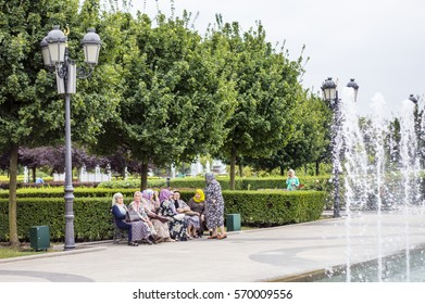 "GROZNY, CHECHNYA, RUSSIA - Aug 16, 2016: Chechen women sitting on the bench near Mosque ""Heart of Chechnya"" (Akhmad Kadyrov Mosque) view in Grozny, the capital of Chechnya, Russia"