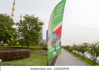 Grozny, Russia: 10.07.2015. Daily life in Chechen Republic. The path in the park near the main mosque of the Chechen Republic - Akhmad Kadyrov Mosque (Heart of Chechnya), decorated with flags