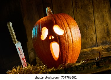 Gruesome Halloween Jack-o-lantern background with a bloodied knife alongside a glowing pumpkin with ghostly face