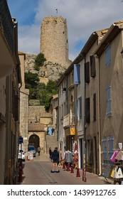 Gruissan, Aude/France - April 28 2019:The first tourists of the season in a typical narrow street in Gruissan with the iconic Barberousse Tower in the background