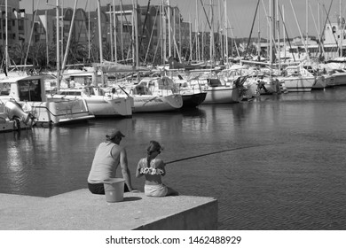 Gruissan, Aude/France - July 18 2019 a timeless image of a father in cap and sleeveless t-shirt and young daughter fishing in the port of Gruissan. Could have been taken today or 20 years ago.