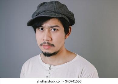 Grumpy Asian man is looking at the camera.