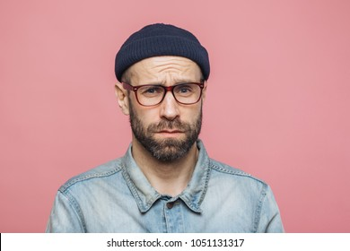 Grumpy bearded man with offended expression, being dissatisfied with something, frowns face, wears spectacles, hat and shirt, isolated over pink background. Displeasure and negativity concept