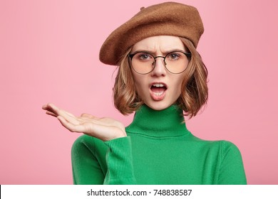 Grumpy irritated female in beret and spectacles, gestures with hand, being emotional and angry after offended by cruel man, recieves bad words, isolated over pink background. Bewilderment concept