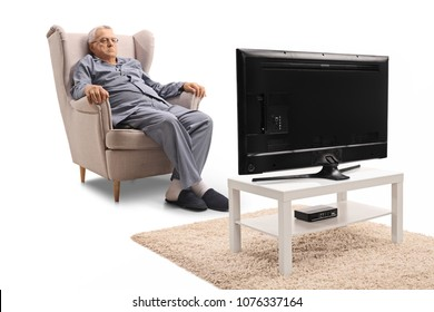 Grumpy mature man in pajamas sitting in an armchair and watching television isolated on white background