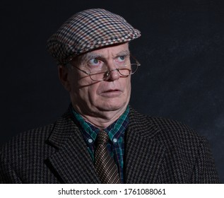 Grumpy old English eccentric gentleman posing for his portrait in his tweeds and sunglasses