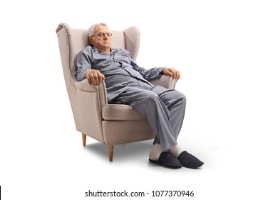 Grumpy old man in pajamas seated in an armchair isolated on white background