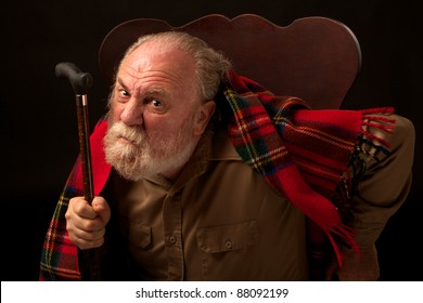 Grumpy old man shakes cane and frowns