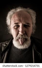 Grumpy senior man showing tongue against dark background