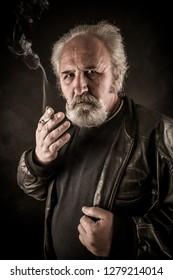 Grumpy senior man smoking cigarette against dark background