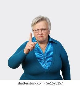 Grumpy senior woman in glasses threatens finger on gray background - grandmother portrait