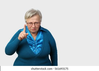 Grumpy senior woman in glasses threatens finger on gray background  with blank copy space for text - grandmother portrait