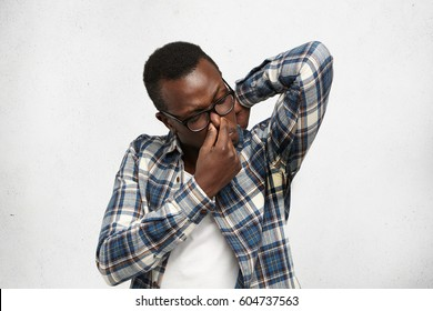 Grumpy stinky young dark-skinned male in glasses and shirt raising elbow, sniffing sweaty armpit with disgusted expression, pinching nose, can't stand unpleasant smell of sweat, posing at white wall