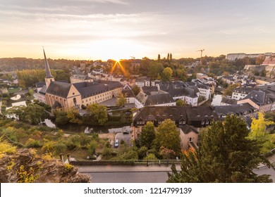 The Grund and part of the Luxembourg Skyline at sunrise. Architecture, rooftops and trees can be seen.