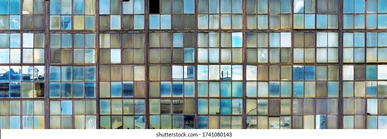 Grunge background of old shop windows of an inactive factory room, traces of aging glass, cracks. Reflections of the blue sky. Aspect ratio 3 to 1.