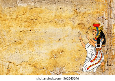 Grunge background with old stucco texture of yellow color and Egyptian goddess Isis image