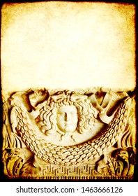Grunge background with paper texture and detail of an ancient carved stone ornament with Medusa Gorgon head. Copy space for text. Mock up template