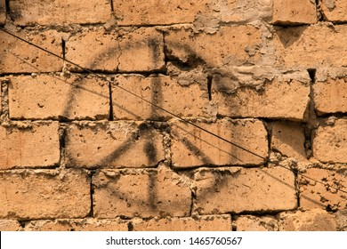 Grunge background of rustic bricks with sloppy mortar with spray painted peace sign and an electric wire running diagonally
