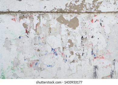 Grunge background texture. The background image is a white shabby wall with traces of multicolored inscriptions and graffitti. Surface in places flaked, sprinkled and there is visible brown plaster.