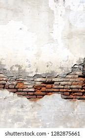 Grunge background with texture of old brick wall and cracked stucco of white color