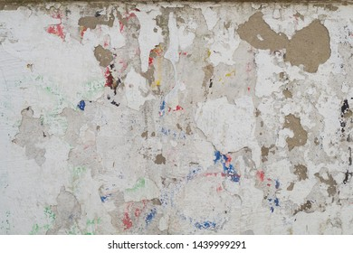 Grunge background texture. The old shabby dirty wall with flaking whitewash and multi-colored graffiti tracks. Urban street youth background.