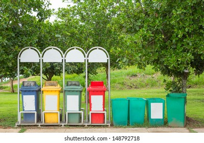 Grunge blue yellow green and red bin on stand near footpath in public park
