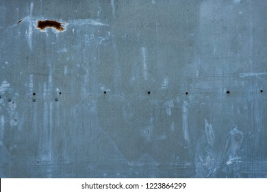 Grunge blue-gray metal sheet with rust patch, rivets, paint and water staining