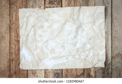 grunge Crumpled paper texture on wooden table surface