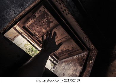 Grunge dark interior with open rusted door and male hand silhouette