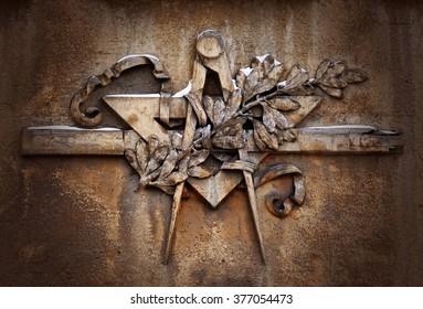 Grunge freemasonry emblem on dramatic background - masonic square and compass symbol, closeup of old architectural building decoration