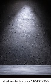 Grunge gray wall and gray plank with spot light from above. Can be used as background