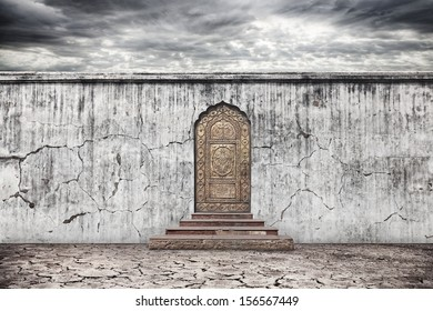Grunge grey wall and vintage door with oriental ornament on dry earth with cracks at dramatic sky background