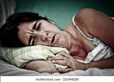 Grunge and gritty portrait of sick woman laying in bed