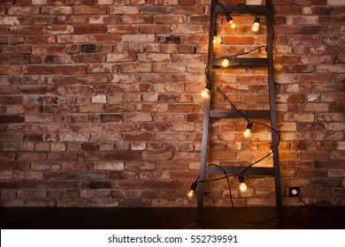 grunge interior with ladder and lamps on a brick wall. Modern grungy interior.