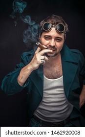 Grunge man, steampunk dressed, smoking a cuban cigar. Black studio background