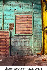 Grunge, old and dirty building interior . Green painted  worn brick wall with deeply detailed and clean brick wall inside like a frame. Contrast abstract background.