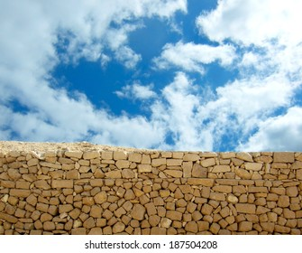grunge old stone wall on background of blue sky