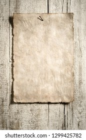 grunge paper sheet on aged wooden wall