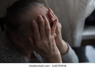 Grunge portrait of an old woman suffering from a headache with a desperate expression