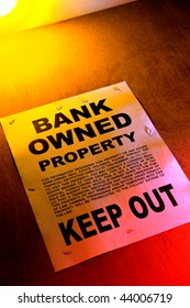 Grunge Real estate lender bank owned keep out sign notice posted on a boarded up foreclosed building in foreclosure (fictitious document with authentic legal language)