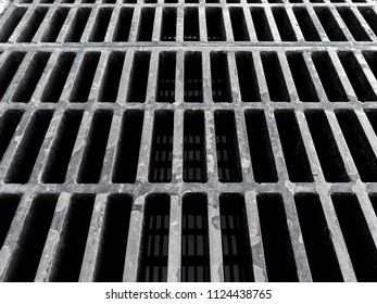 Grunge steel grating on the road ground to drain water from the road