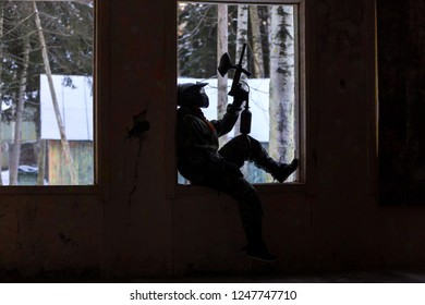 Grunge style dark silhouette of paintball player sitting on window sill